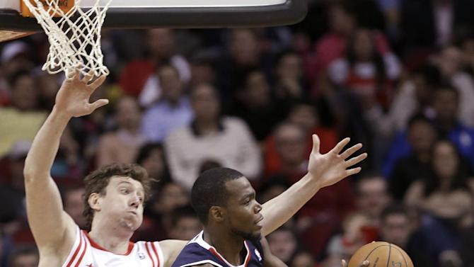 Atlanta Hawks' Paul Millsap, right, passes the ball in front of Houston Rockets' Omer Asik (3) in the second half of an NBA basketball game Wednesday, Nov. 27, 2013, in Houston. The Rockets won 113-84