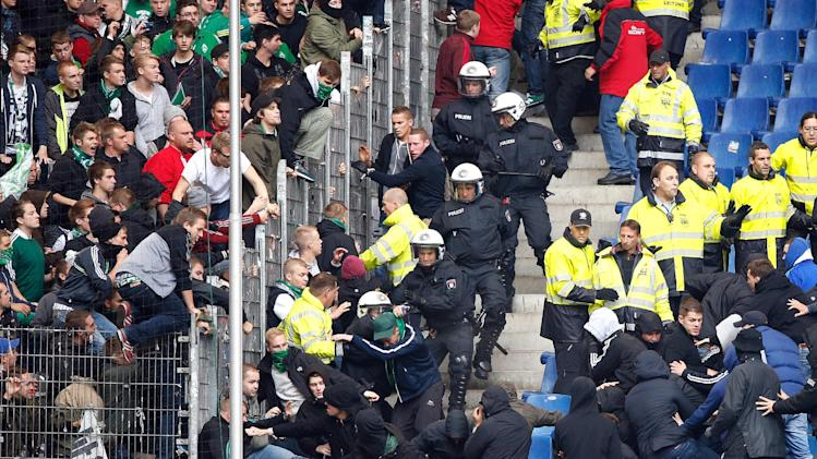 Police officers and security personell try to stop fans of Hamburger SV , right, wanting to raid the fan area of Bremen, left,  at the stands  prior to  the Bundesliga soccer match between Hamburger SV and Werder Bremen a  in Hamburg, Germany,  Saturday Sept. 21, 2013