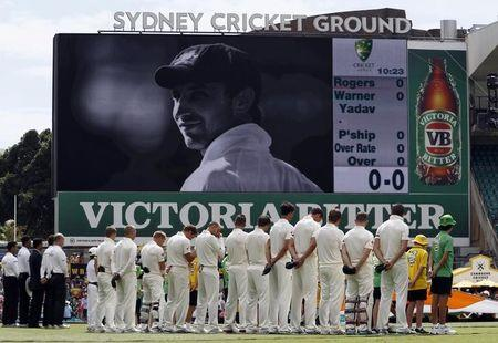 Australia's Nathan Lyon reacts with team mates and officials during a ceremony in memory of team mate Phillip Hughes before the start of the first day's play in the fourth test against India a