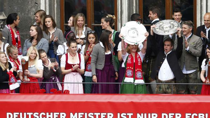 Bayern Munich's player Lahm and Bayern Munich's women's team player Behringer hold the trophies as they celebrate winning the German Bundesliga title in front of the town hall, in downtown Munich