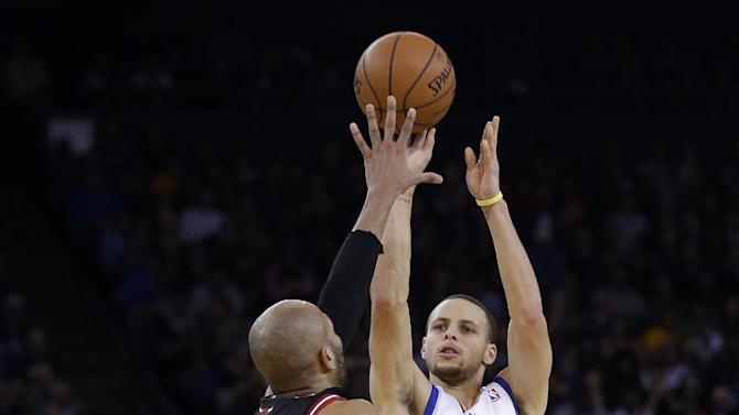 Golden State Warriors' Stephen Curry (30) makes a three-point basket over Chicago Bulls' Taj Gibson during the second half of an NBA basketball game on Thursday, Feb. 6, 2014, in Oakland, Calif. Golden State won 102-87