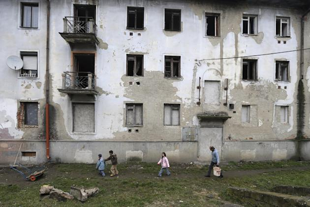 In this March 2, 2015 photo, residents walk past their house in a Roma settlement in Kralovsky Chlmec, Slovakia. Each year, dozens of women from the poorer corners of eastern Europe are lured to trave
