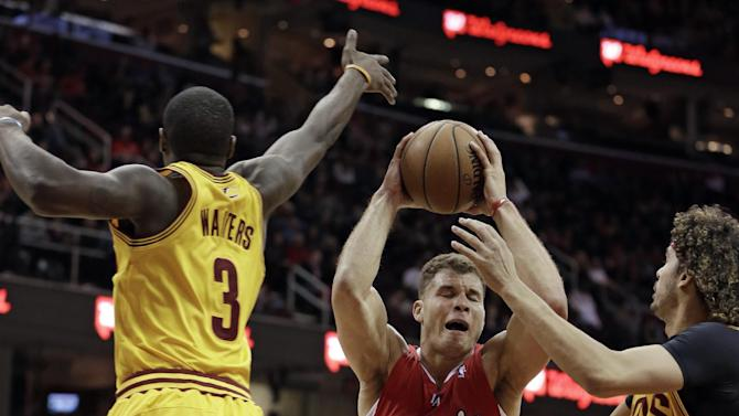Los Angeles Clippers' Blake Griffin (32) tries to squeeze between Cleveland Cavaliers' Dion Waiters (3) and Anderson Varejao (17), from Brazil, during the second quarter of an NBA basketball game on Saturday, Dec. 7, 2013, in Cleveland