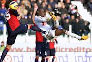 AC Milan's forward Mario Balotelli (R) kicks the ball past Cagliari's defender Luca Rossettini (L) during their Italian Serie A football match at Cagliari's Is Arenas stadium on February 10, 2013. The match ended in a 1-1 draw