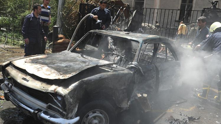 In this photo released by the Syrian official news agency SANA, Syrian firefighters extinguish a burning car, at the scene of a powerful explosion which occurred in the central district of Marjeh, Damascus, Syria, Tuesday April 30, 2013. A powerful explosion rocked Damascus on Tuesday, causing scores of casualties, a day after the country's prime minister narrowly escaped an assassination attempt in the heart of the heavily protected capital. (AP Photo/SANA)