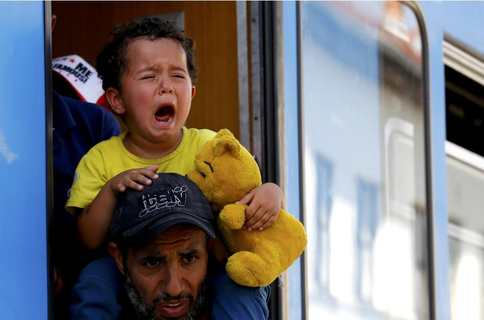 A migrant child cries as migrants scramble aboard a train at the station in Beli Manastir