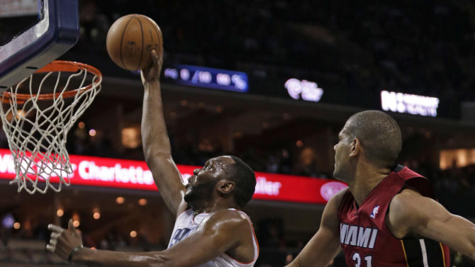 Charlotte Bobcats' Al Jefferson, left, drives past Miami Heat's Shane Battier, right, to dunk during the first half of an NBA basketball game in Charlotte, N.C., Saturday, Jan. 18, 2014. (AP Photo/Chuck Burton)