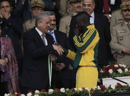 JS Kabylie striker Albert Ebosse, from Cameroon, shakes hands with Algeria's Prime Minister Abdelmalek Sellal (L) after being defeated during the Algeria Cup final soccer match against MC Alger in Algiers May 1, 2014. REUTERS/LOUAFI LARBI
