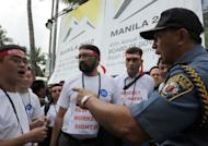 A Philippine policeman (R) argues with foreign delegates to the Asian Development Bank board of governors annual meeting as they held a silent protest in support of workers rights in front of the venue of the meeting, in Manila