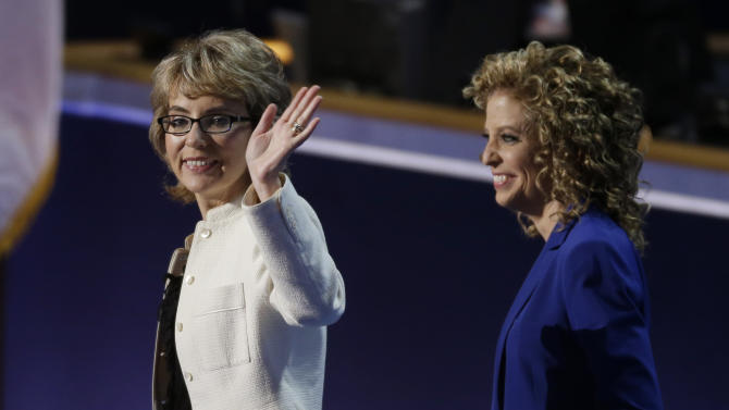 Former Rep. Gabrielle Giffords, left, waves with Democratic National Committee Chairwoman Rep. Debbie Wasserman Schultz, from Florida, after reciting the Pledge of Allegiance the Democratic National Convention in Charlotte, N.C., on Thursday, Sept. 6, 2012.(AP Photo/Lynne Sladky)