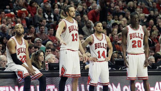 Chicago Bulls forward Taj Gibson (22), center Joakim Noah (13), guard D.J. Augustin (14) and forward Tony Snell (20) react during the second half of an NBA basketball game against the Dallas Mavericks in Chicago on Saturday, Dec. 28, 2013. The Mavericks won 105-83