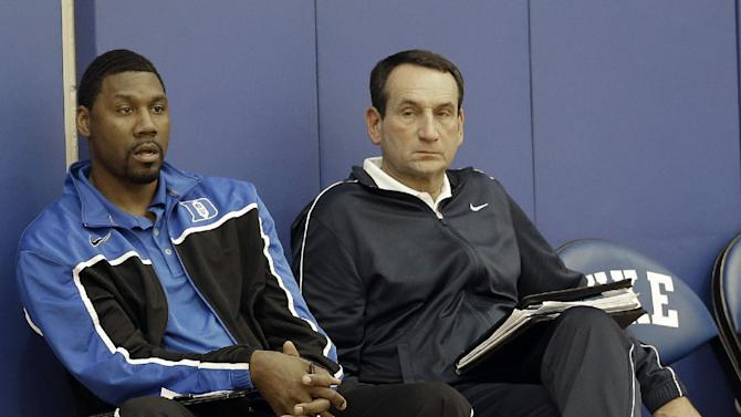 Duke coach Mike Krzyzewski, right, and assistant coach Nate James watch as the Brooklyn Nets work out during NBA basketball training camp at Duke University in Durham, N.C., Tuesday, Oct. 1, 2013