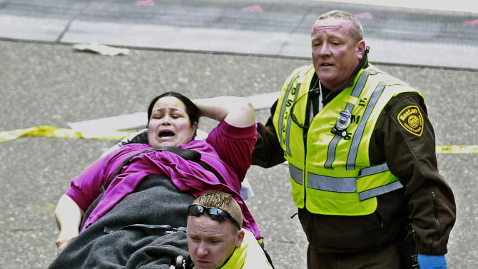 Medical workers aid an injured woman at the finish line of the 2013 Boston Marathon following two explosions there, Monday, April 15, 2013 in Boston. Two bombs exploded near the finish of the Boston Marathon on Monday, killing at least two people, injuring at least 23 others and sending authorities rushing to aid wounded spectators. (AP Photo/Charles Krupa)