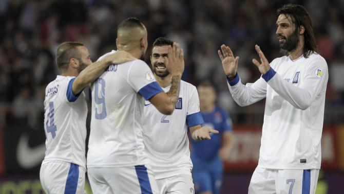 Greece's players celebrate Slovakia's own goal during the 2014 World Cup qualifying soccer match at Karaiskaki stadium in Piraeus near Athens