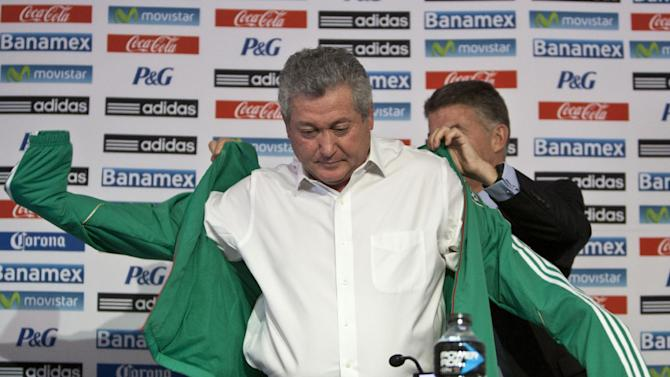 "Victor Manuel Vucetich puts on his new team's jacket with the help of Hector Gonzalez Inarritu, the director of Mexico's national soccer teams, as Vucetich is named the new coach for Mexico's national soccer team in Mexico City, Thursday, Sept. 12, 2013.  Vucetich is one of the most successful coaches in the local league, where hes known as ""King Midas"" after winning 14 of 15 the finals he has managed in his career.  He replaces Jose Manuel De la Torre who was fired on Saturday after a loss to Honduras"