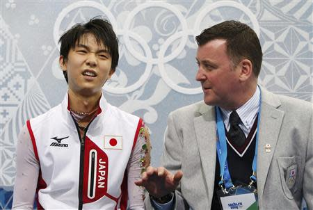 "Japan's Yuzuru Hanyu reacts with coach Brian Orser in the ""kiss and cry"" area during the Figure Skating Men's Free Skating Program at the Sochi 2014 Winter Olympics, February 14, 2014. REUTERS/Lucy Nicholson"