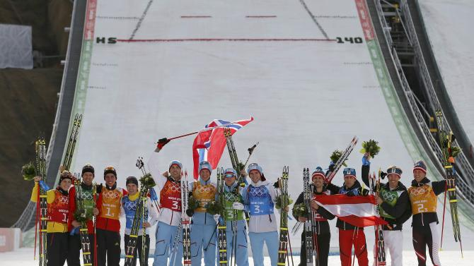 Germany's second placed team members, Norway's winning team members and Austria's third placed team members celebrate after the flower ceremony for the of the Nordic Combined team Gundersen event of the Sochi 2014 Winter Olympic Games