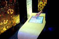 Technology and tradition: A visitor uses a touch-screen display to find out about the story of batik in front of him. (