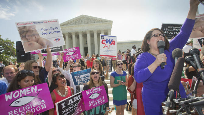 Kristin Hughs, right, announces to supporters the Supreme Court's decision on the Hobby Lobby case in Washington, Monday, June 30, 2014. The Supreme Court says corporations can hold religious objections that allow them to opt out of the new health law requirement that they cover contraceptives for women.(AP Photo/Pablo Martinez Monsivais)