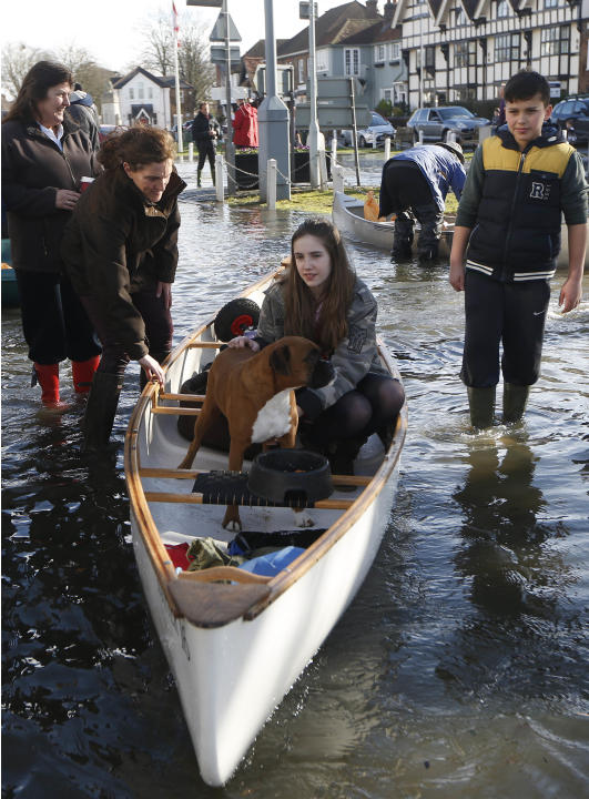 A girl sits with her dog in a boat on a flooded street, in Datchet, England, Monday, Feb. 10, 2014. The River Thames has burst its banks after reaching its highest level in years, flooding riverside t