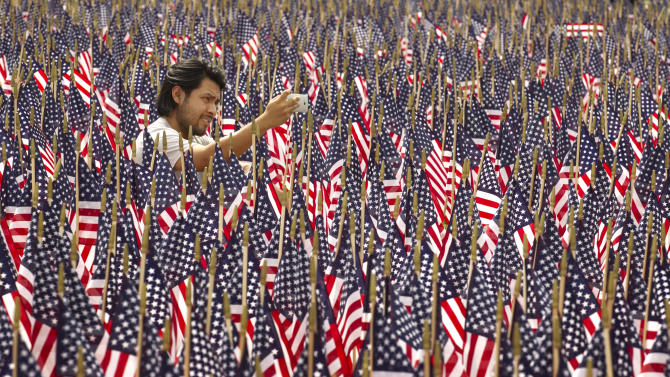 "Edgar Yepez takes a photo among 7,000 American flags on display outside the Long Center in Austin, Texas, on Memorial Day, Monday, May 27, 2013. The flags are in honor of the fallen veterans of the wars in Iraq and Afghanistan.  The display was organized by Operation Honor Our Heroes, an organization that was founded by Nancy Glass after her friend MSG Robert M. Horrigan was killed in Iraq in 2005.  ""I feel very honored to be part of this celebration,""  said Yepez, 28, who was born in Mexico to a Mexican mother and Pakistani father. (AP Photo/Austin American-Statesman, Jay Janner)"