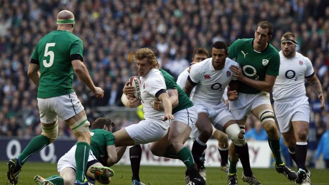 England's Billy Twelvetrees (centre) is tackled during the Six Nations Rugby Union International match between England and Ireland at Twickenham Stadium, in west London, Saturday Feb. 22, 2014. (AP Photo / Jonathan Brady /PA) UNITED KINGDOM OUT