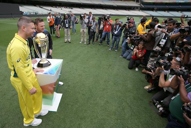 New Zealand's captain Brendon McCullum, second left, and Australia's captain Michael Clarke, left, pose for a photo of the Cricket World Cup trophy at the Melbourne Cricket Ground in Melbourne