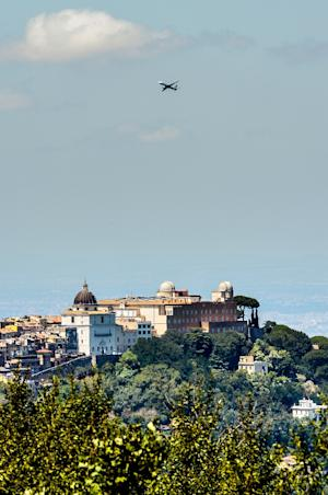 A plane flies over the telescope domes of the Vatican …