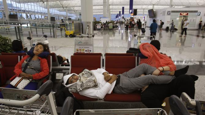 Passengers whose flights are cancelled in anticipation of typhoon Usagi rest at Hong Kong Airport