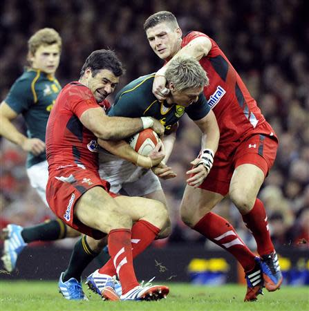 Wales' Phillips and Williams tackles South Africa's De Villiers during the international rugby union match in Cardiff
