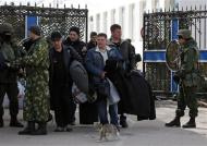 People, believed to be Ukrainian servicemen, carry their belongings as they walk past armed men, believed to be Russian servicemen, on their way out of the naval headquarters after it was taken over by pro-Russian forces in Sevastopol, March 19, 2014. REUTERS/Vasily Fedosenko