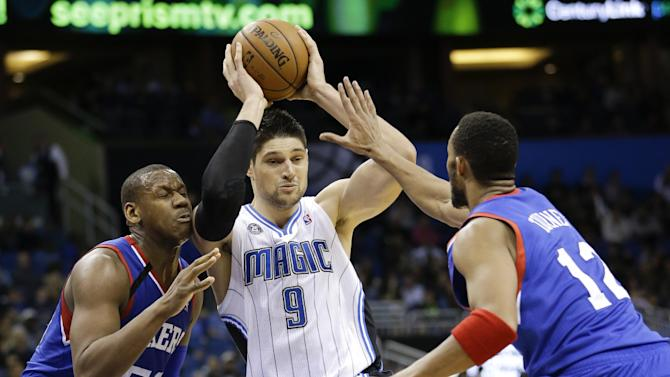 Orlando Magic's Nikola Vucevic (9), of Montenegro, passes the ball as he is caught between Philadelphia 76ers' Lavoy Allen, left, and Evan Turner (12) during the second half of an NBA basketball game in Orlando, Fla., Wednesday, Nov. 27, 2013. Orlando won  105-94