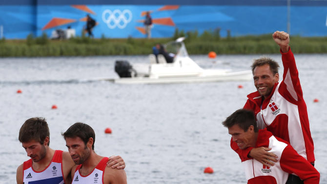 Gold medallists Rasmussen and Quist of Denmark celebrate next to silver medallists Purchase and Hunter of Britain after competing in the men's lightweight double sculls final during the London 2012 Olympic Games at Eton Dorney