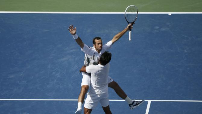 Paes of India and Stepanek of the Czech Republic celebrate winning match point against Bob and Mike Bryan of the U.S. in their men's doubles match at the U.S. Open tennis championships in New York