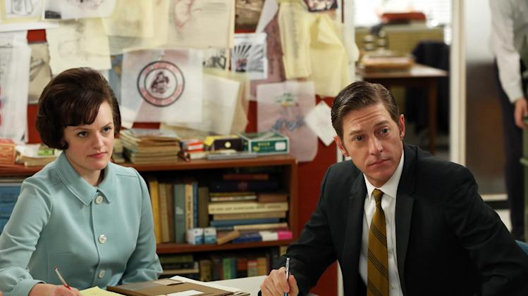 "This undated publicity image released by AMC shows  Elisabeth Moss as Peggy Olson, left, and Kevin Rahm as Ted Chaough in a scene from "" Mad Men.""  Rahm's character appeared in a handful episodes in past seasons as the boss of a competing advertising firm. But the recent merger of his and Don Draper's companies _ along with a shocking kiss with Peggy Olson (Elisabeth Moss) _ has thrust Ted to the forefront of the 1960s ad world drama. (AP Photo/AMC, Michael Yarish)"