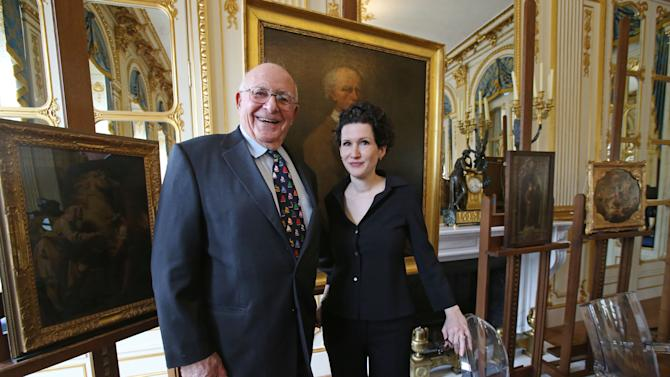 American Thomas Selldorff, left, and Austrian art historian, Sophie Lillie, who helped him to identify the paintings, pose for the media during a ceremony at the Culture Ministry in Paris, France, Tuesday, March 19, 2013, to return seven paintings taken from their Jewish owners during World War II, as part of ongoing efforts to give back hundreds of looted artworks that still hang in the Louvre and other French museums. Selldorff reclaimed six German and Italian paintings that his grandfather, Richard Neumann, was forced to sell during World War II to flee Nazi occupation, and another painting was returned to other recipients. In the background are some of the returned paintings. (AP Photo/Michel Euler)