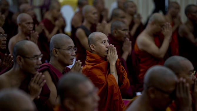 In this Thursday, June 13, 2013 photo, controversial Buddhist monk Wirathu, center, who is accused of instigating sectarian violence between Buddhists and Muslims through his sermons, performs Buddhist rituals during an assembly of Myanmar's powerful Buddhist clergy in Hmawbi, outskirts of Yangon, Myanmar. Wirathu is a charismatic speaker and supporter of the fundamentalist 969 movement. His following is growing as he crisscrosses the country calling for boycotts of Muslim-owned shops and a ban on marriages between Buddhist women and Muslim men, and warning that a higher birthrate could one day bring Muslims from 4 percent of the population to a majority. (AP Photo/Gemunu Amarasinghe)