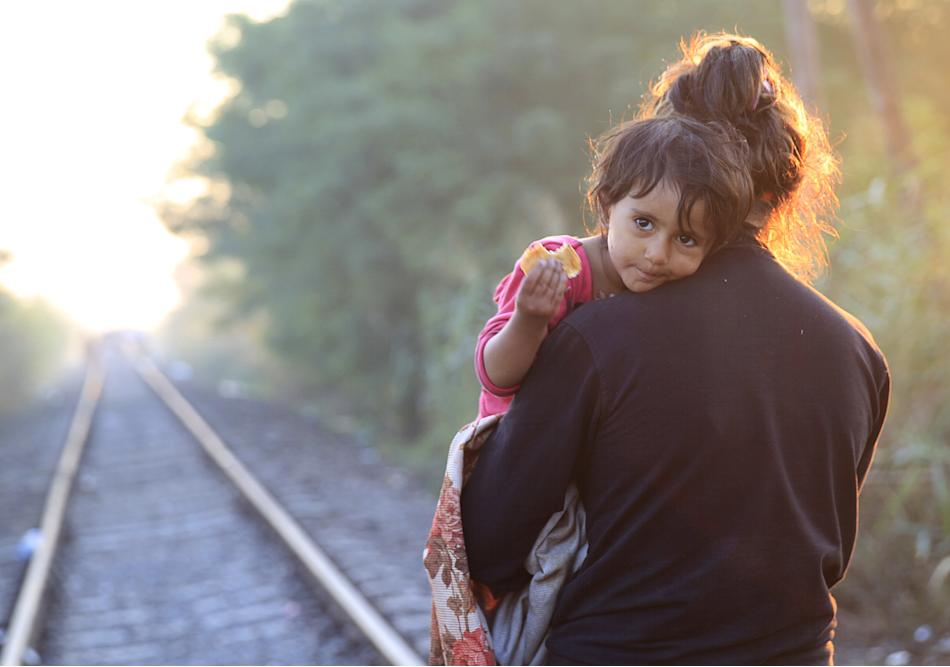 A Syrian migrant carries a child as she walks along a railway track after crossing into Hungary from the border with Serbia, at early morning near Roszke