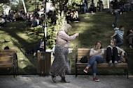 A traditionally-veiled Turkish woman sells whistles to young activists sitting at Kugulu Park in Ankara on June 7, 2013. Hotel reservations may be down after a week of violent mass protests in Turkey, but plucky tourists on the ground have taken the unrest in their stride