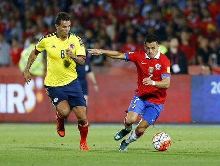 Sanchez of Chile fights for the ball with Cardona of Colombia during their 2018 World Cup qualifying soccer match in Santiago, Chile.