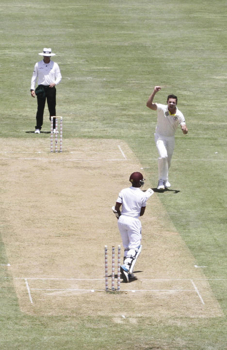 Australia's bowler Josh Hazlewood, right, celebrates after taking the wicket of West Indies' Jermaine Blackwood, bottom, who was caught by the Australia's Mitchell Starc for two runs, duri