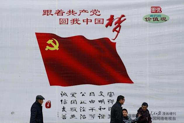 In this Friday, Feb. 27, 2015 photo, a Chinese family walk past a China Dream billboard, showing messages pushed by Chinese President Xi Jinping's administration on display in Beijing. China on Sa