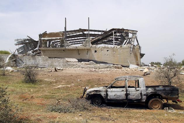 Damaged vehicle is seen in front of a destroyed building at Qarmeed camp, after Islamist rebel fighters took control of the area from forces of Syria's President Assad