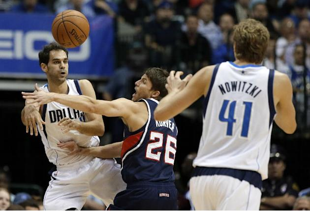 Dallas Mavericks point guard Jose Calderon, left, of Spain, passes the ball to Dirk Nowitzki (41), of Germany, as Atlanta Hawks forward Kyle Korver (26) defends in the first half of an NBA basketball