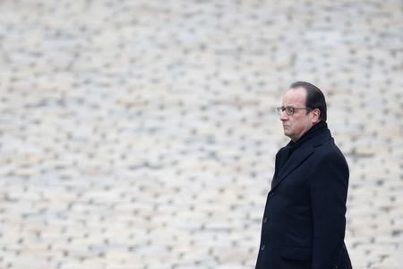French President Francois Hollande stands at attention during a ceremony to pay a national homage to the victims of the Paris attacks at Les Invalides monument in Paris, France, November 27, 2015. REUTERS/Charles Platiau