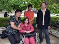 China's disabled rights activist Ni Yulan (centre) and her husband Dong Jiqin (orange shirt) pose with friends at Beijing's Imperial City Heritage Park in 2010. Ni Yulan has been beaten, barred from practising law, and repeatedly jailed for fighting the forced evictions of thousands to make way for Beijing's Olympic makeover