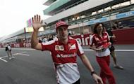 Ferrari Formula One driver Fernando Alonso of Spain waves to his fans at the Buddh International Circuit in Greater Noida on the outskirts of New Delhi October 24, 2013. REUTERS/Adnan Abidi