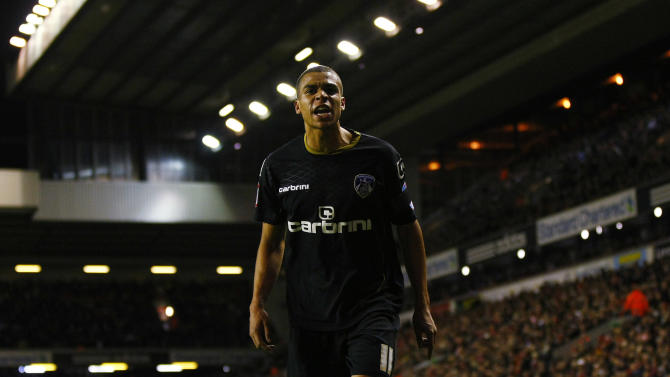 Oldham Athletic's Tom Adeyemi  reacts during their FA Cup third round soccer match at Anfield, Liverpool, England, Friday Jan. 6, 2012. The police are investigating an incident in which a black Oldham player appeared to be the target of abuse from Liverpool fans during an FA Cup third-round match on Friday. Oldham right back Tom Adeyemi was visibly upset late in the game at Anfield after seemingly taking offence from something shouted from the Liverpool-supporting area known as The Kop. (AP Photo/Tim Hales)
