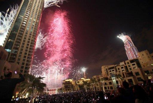 Fireworks illuminate Burj Khalifa while thousands of people gather to celebrate the New Year at midnight in Dubai on January 1, 2013