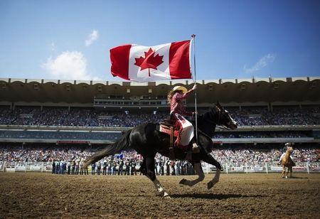 A Calgary Stampede rodeo girl carries Canadian flag during singing of national anthem during day 2 of Calgary Stampede rodeo in Calgary